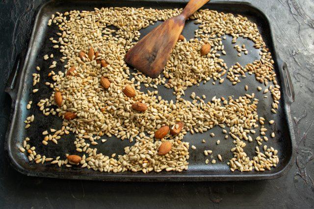 Добавляем к семечкам миндальные орехи и отправляем противень в духовку