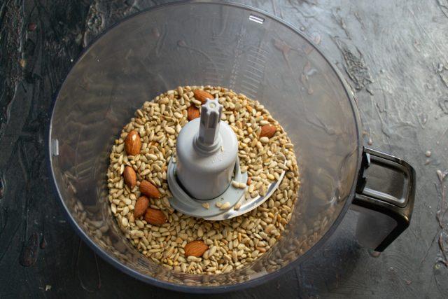 Обжаренные семечки и орехи пересыпаем в чашу кухонного комбайна